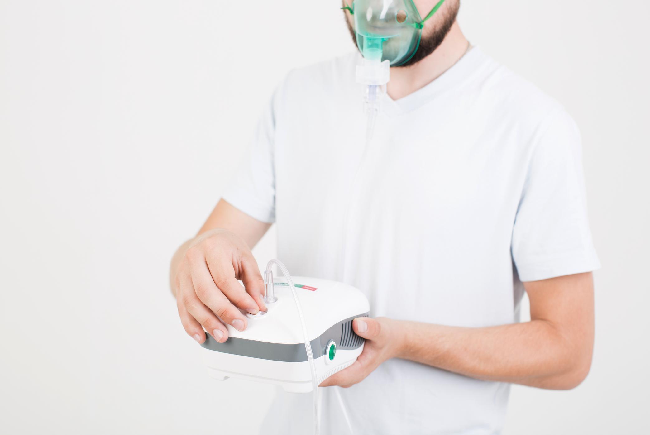 Pria menggunakan alat nebulizer