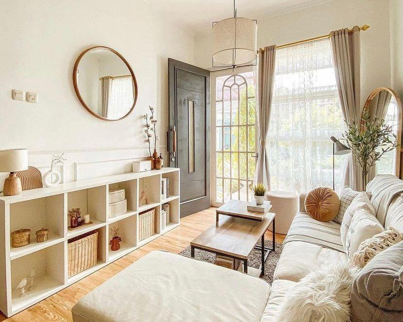 ruang tamu dengan cermin bulat dan rak
